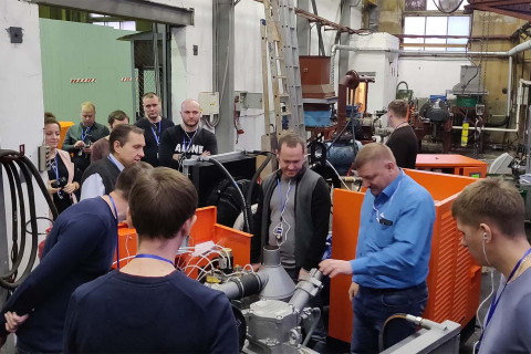 """Visit of a group of students from Gazpromneft Khantos, Gazpromneft Yamal, Gazpromneft Orenburg, Gazpromneft Vostok and Messoyakhaneftegaz in the framework of the training course of the center """"Compressor, vacuum, compressor equipment and pneumatic systems"""" to the Arsenal machine building plant. At the photo, a group of students with the Director of the center Sergey Kartashev at the site of acceptance tests of the Arsenal machine-building plant."""